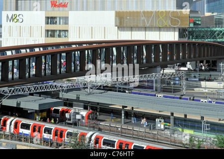Westfield Shopping Centre entrance bridge & aerial view tube train at Stratford station platform M&S sign on Marks - Stock Photo