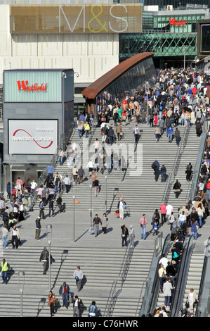Aerial view crowds of people queue at Westfield Shopping Centre entrance steps & escalators below M&S sign lifestyle - Stock Photo
