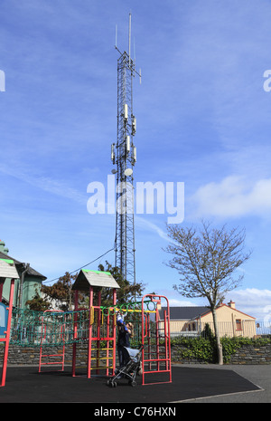 A mother plays with her young son in a playground under a telecommunications mast in Castletownbere, Co Cork, Rep - Stock Photo