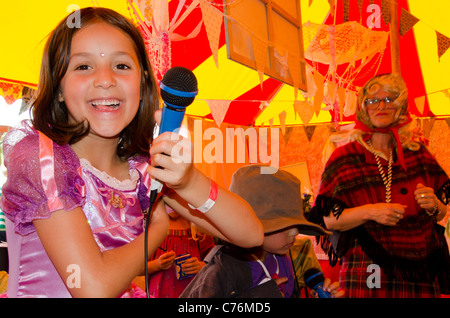 young girl in fancy dress facing camera holding a microphone at the Shambala Festival 2011 - Stock Photo