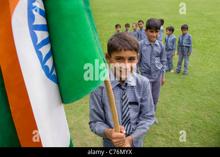 Portrait of a school boy holding the Indian flag - Stock Photo