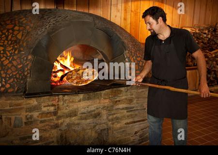 chef Bryan Collins cooks a pepperoni and pasilla chile pizza in oven, Flatbread, Los Alamos, California,United States - Stock Photo