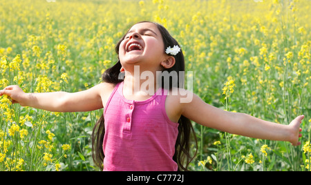 Young girl enjoying herself in a field - Stock Photo