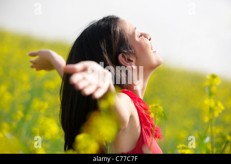 Young woman enjoying herself in a field - Stock Photo