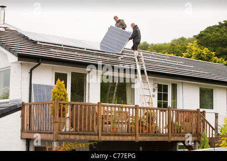Technicians fitting solar photo voltaic panels to a house roof in ...