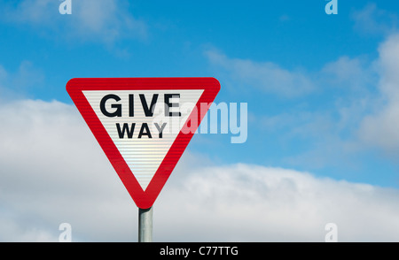 Give way warning road sign against blue cloudy sky. England - Stock Photo