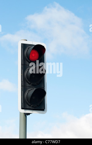 Red Traffic light against blue sky in England - Stock Photo
