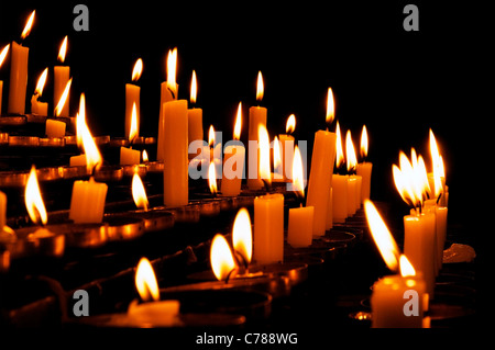 Burning prayer candles in a catholic church in Europe - Stock Photo