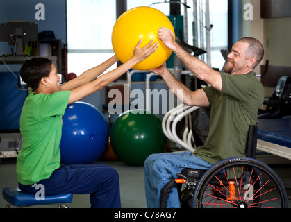 A physical therapist works with a patient in the rehab room. - Stock Photo