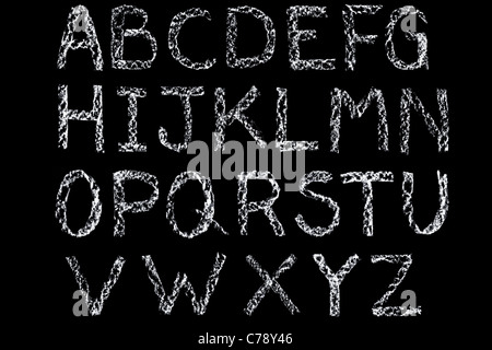 Handwritten letters of the alphabet written on a blackboard in white chalk then cleaned up during editing - Stock Photo