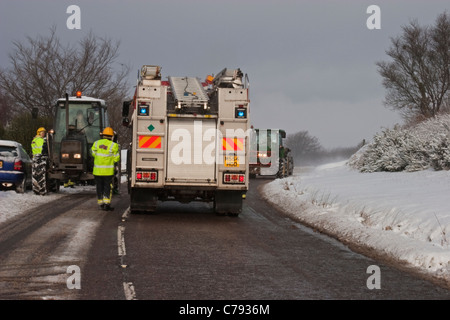 Trunk-road blocked in heavy snow after a vehicle went off the road. Local tractors and fire crew assist. - Stock Photo