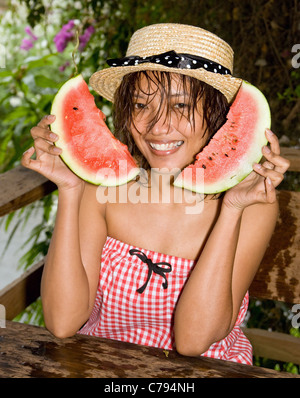 Young woman holding a fresh water melon - Stock Photo