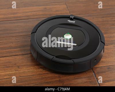 iRobot Roomba 770 household vacuum cleaning robot on hardwood floor - Stock Photo