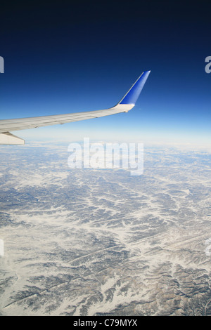 view from an airplane flying over winter mountains with the airline wing visible - Stock Photo