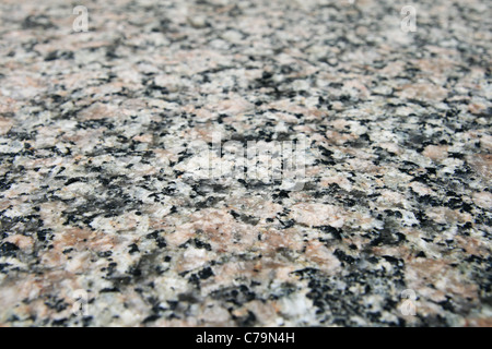 granite rock surface viewed from an angle with selective focus and shallow depth of field - Stock Photo
