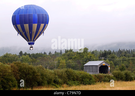 A hot air balloon flies over Plumweseep Covered Bridge at the Atlantic International Balloon Fiesta Sept. 9, 2011 - Stock Photo