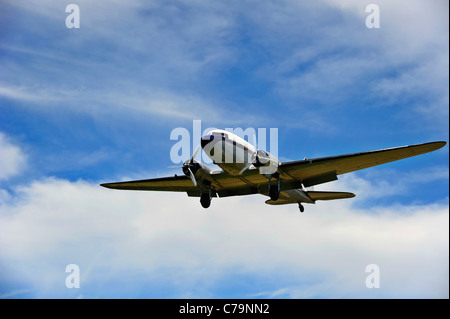 A vintage Douglas DC-3A coming in to land at an airfield - Stock Photo