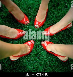 USA, Utah, Salt Lake City, Close-up on six women feet in red peeptoe shoes - Stock Photo