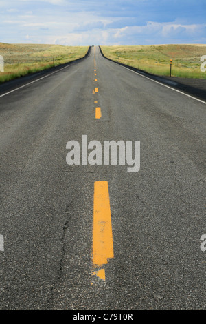 a car approaches through the heat haze on a road in Wyoming - Stock Photo
