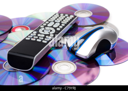 Remote control and computer mouse over a bed of dvd disks isolated over white. - Stock Photo