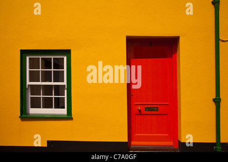 The front of a terraced house with a red door and green windows in Lyme Regis in Dorset - Stock Photo