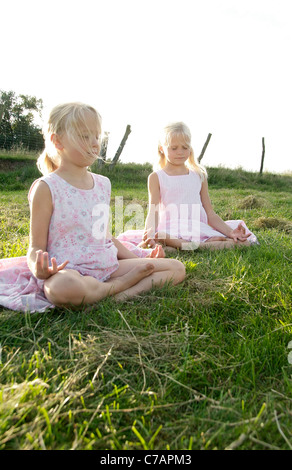 Portrait of two girl friends practicing yoga in summer, Eyendorf, Lower Saxony, Germany, Europe - Stock Photo