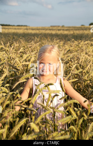 Girl, 6 years old, wearing a dress in a wheat field in summer, Eyendorf, Lower Saxony, Germany, Europe - Stock Photo