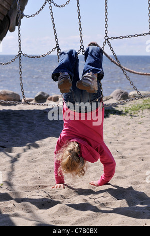 Small 6-year-old blonde girl on a playground in Westerland, Sylt Island, Germany, Europe - Stock Photo