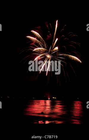 Beautiful fireworks going off over the dark night sky reflecting over the water. - Stock Photo