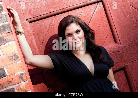 A pretty young woman in a black dress leaning against an old doorway. - Stock Photo