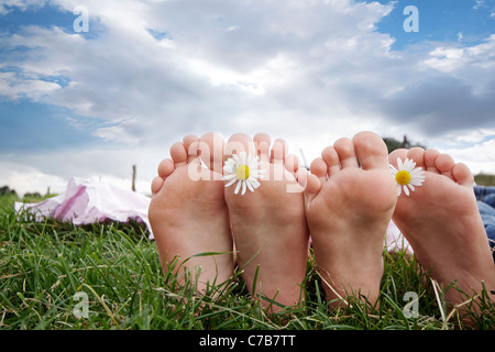 Children playing and relaxing on a meadow in summer, barefoot, Eyendorf, Lower Saxony, Germany, Europe - Stock Photo