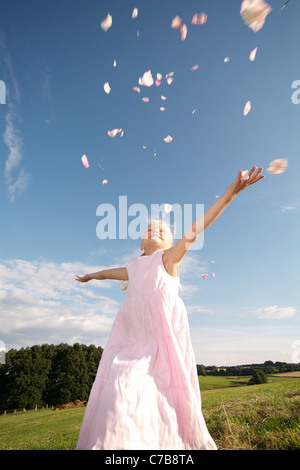Girl scattering petals in the air in summer, Eyendorf, Lower Saxony, Germany, Europe - Stock Photo
