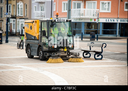 a small compact Schmidt Swingo 200 roadsweeper cleaning the pavement on Aberystwyth promenade UK - Stock Photo