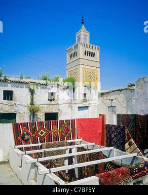 Tunis, Tunisia, North Africa, old Medina, hand-woven carpets display on roof terrace, Zitouna mosque minaret, - Stock Photo