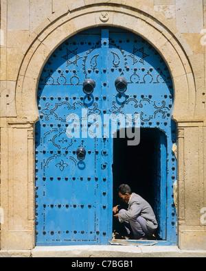 Sidi Bou Said, Tunisia, North Africa, carpenter repairing a traditional blue studded door, - Stock Photo