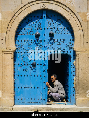 Sidi Bou Said, Tunisia, North Africa, carpenter repairing a traditional blue studded door at an arched doorway, - Stock Photo