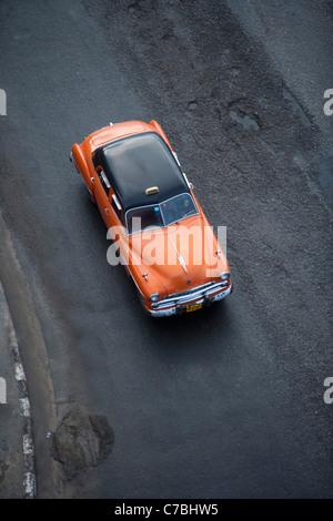 Orange vintage American car taxi on Malecon sea wall, City of Havana, Havana, Cuba - Stock Photo