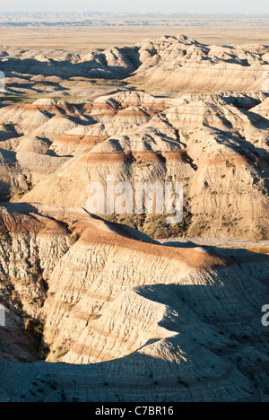 Early morning sunlight shines on sculpted spires and buttes in the Badlands National Park in South Dakota. - Stock Photo