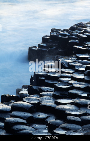 Waves splashing over basalt columns near sunset, Giant's Causeway, County Antrim, Northern Ireland, United Kingdon - Stock Photo
