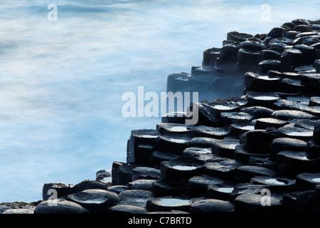 Waves splashing over basalt columns near sunset, Giant's Causeway, County Antrim, Northern Ireland, United Kingdon - Stock Photo