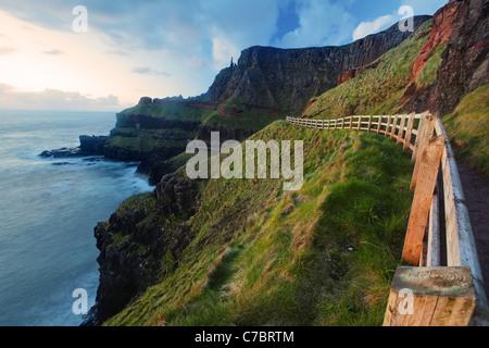 Fenced cliffside trail on Benbane Head near sunset, Giant's Causeway, County Antrim, Northern Ireland, United Kingdon - Stock Photo