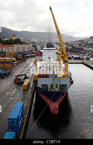 Freight containers being loaded onto the cargo container ship, MV Celina, in the port of Bergen, Norway. - Stock Photo