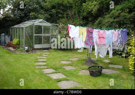 Garden greenhouse, small lawn paving and washing line with washing - Stock Photo