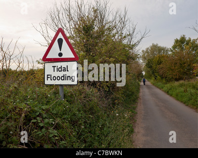 Man walking down a small country lane with a sign showing road liable to tidal flooding - Stock Photo