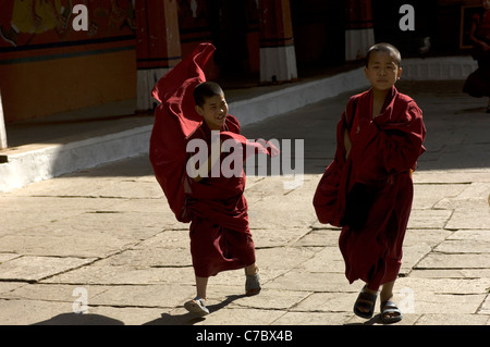 As they cross the courtyard of their monastery in Bhutan, the robes of two young apprentice monks are blown out - Stock Photo