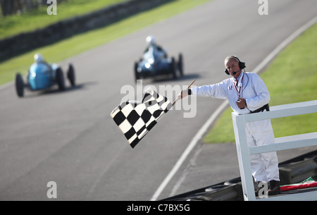 Cars speed past the checkered flag at the Goodwood Revival Meeting 2011. Picture James Boardman. - Stock Photo