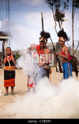 India, Nagaland, Longwa, Konyak Naga warrior in traditional dress, firing hand made muzzle loading gun - Stock Photo