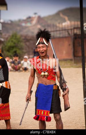 India, Nagaland, Longwa, Konyak Naga warrior in traditional dress, holding hand made muzzle loading guns - Stock Photo