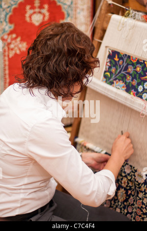 Woman working at a carpet loom in Kusadasi Turkey - Stock Photo