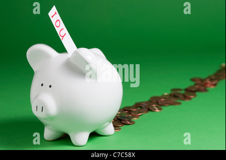 Group of pigs with IOU's coming out of coin slots and pennies coming out back - Stock Photo